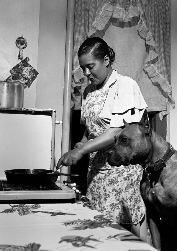 musa do jazz Billie Holiday fritando um bife ao lado de seu cão Mister na cozinha do apartamento onde morou no Harlem, em Nova York. A foto é de Herman Leonard