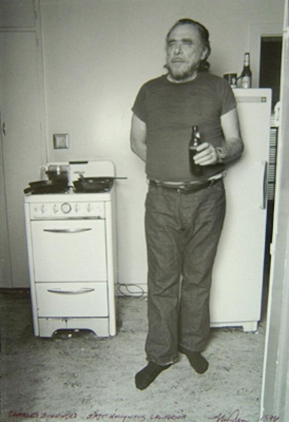 Bukowski fazendo pose junto ao fogão