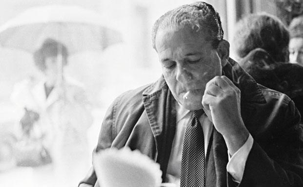 Jango fuma e lê, do outro lado da fronteira, sem poder voltar ao Brasil