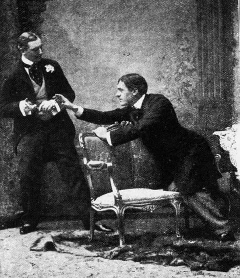 """Cena do primeiro ato da apresentação de estreia de """"A importância de ser prudente"""". Em pé, o ator Allen Aynesworth na pele de Algenor Moncrieff. Sentado está Sir George Alexander como Mr. Jack Worthing."""