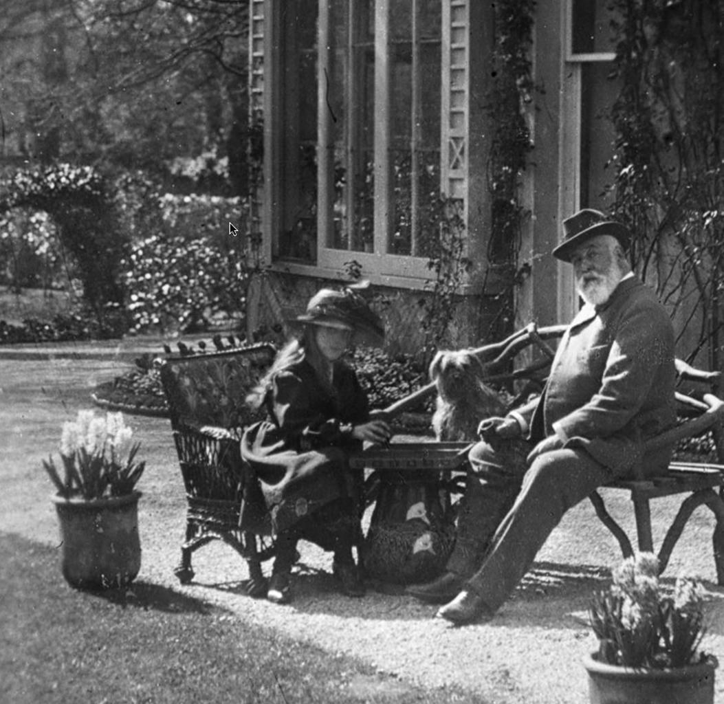 A jovem Agatha joga um jogo de tabuleiro com seu pai no jardim de casa